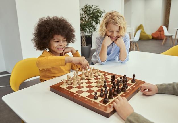 Lächelnde kleine, vielfältige jungen, die zusammen am tisch sitzen und in der schule schach spielen