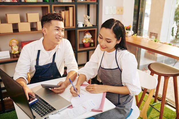 Lächelnde kleinunternehmer, die caférechnungen, ausgaben und steuern am tisch berechnen