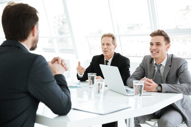 Lächelnde kluge geschäftsleute, die an einem schwierigen finanzprojekt im büro arbeiten