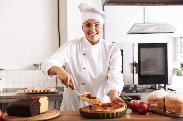 Lächelnde köchin der uniform der uniform, die gekochten kuchen zeigt, während sie an der küche steht