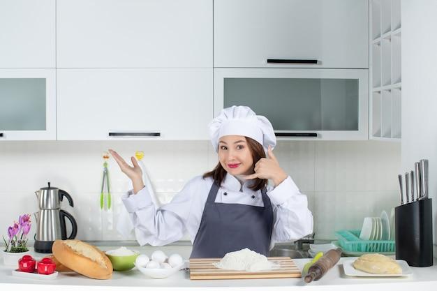 Lächelnde köchin in uniform, die hinter dem tisch mit schneidebrett-brotgemüse steht, die mich in der weißen küche anruft