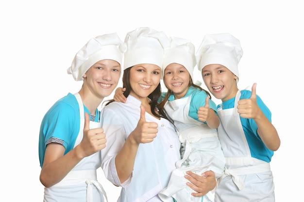 Lächelnde köchin mit assistenten, die daumen nach oben zeigen