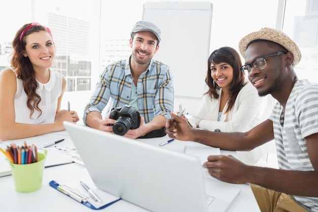 Lächelnde kollegen, die mit digitalkamera arbeiten