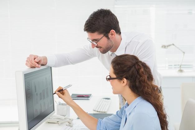 Lächelnde kollegen, die zusammen an computer arbeiten
