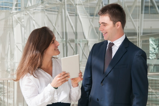 Lächelnde kollegen, frau, die daten bezüglich der tablette zeigt