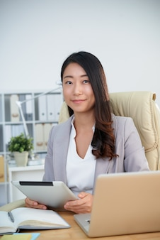 Lächelnde koreanische geschäftsdame, die im büro mit tablette vor laptop aufwirft