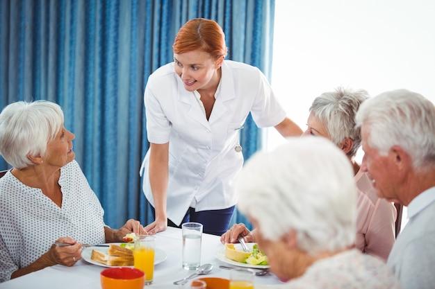 Lächelnde krankenschwester, die ältere person während des frühstücks betrachtet