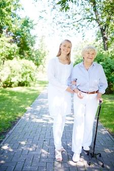Lächelnde krankenschwester, die helfen, reife frau
