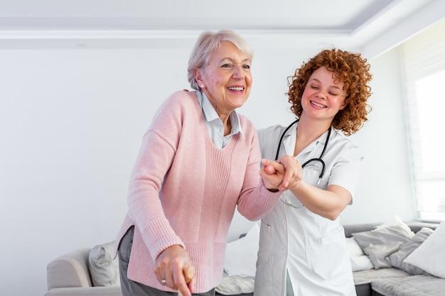 Lächelnde krankenschwester hilft älterer dame, um das pflegeheim herumzulaufen.