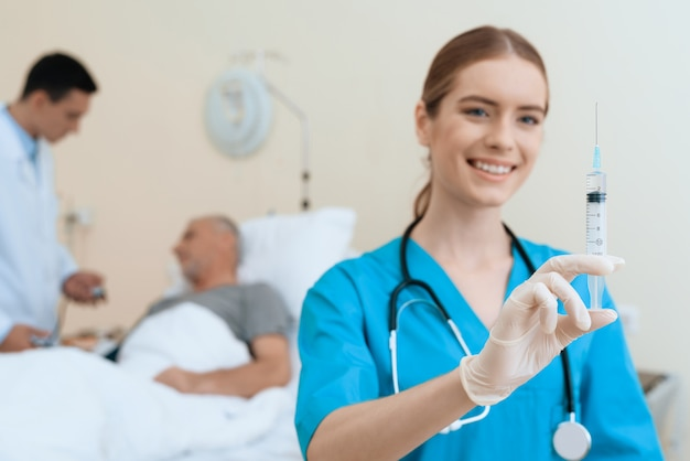 Lächelnde krankenschwester holds injection.