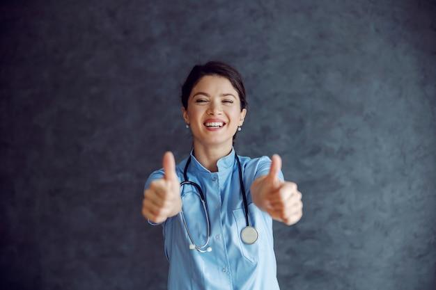 Lächelnde krankenschwester mit stethoskop um hals, kamera betrachtend und daumen hoch zeigend