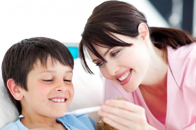 Lächelnde krankenschwester und sein patient, die einen thermometer betrachten