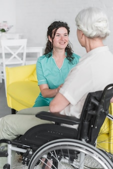 Lächelnde krankenschwester, welche die behinderte ältere frau sitzt auf rollstuhl stützt