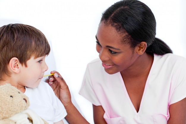 Lächelnde krankenschwester, welche die temperatur des kleinen jungen nimmt