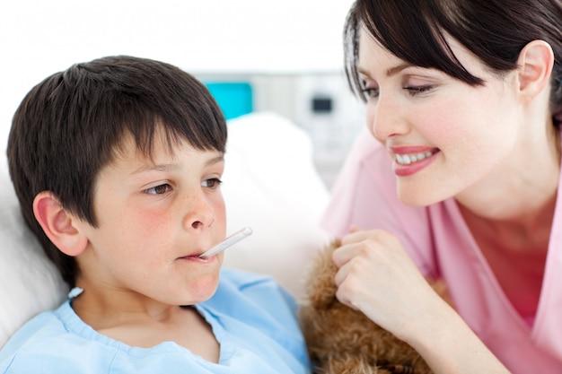 Lächelnde krankenschwester, welche die temperatur ihres patienten nimmt