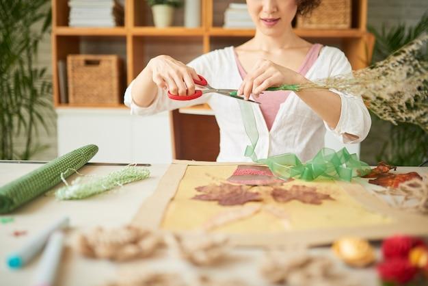 Lächelnde kreative junge frau, die einen strauß getrockneter wildblumen mit nylonband schmückt, wenn sie o...