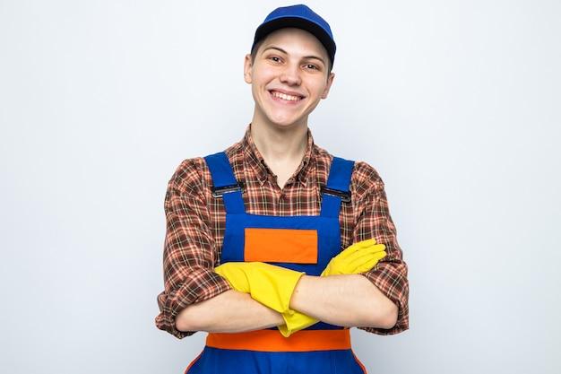 Lächelnde kreuzende hände junger putzmann in uniform und mütze mit handschuhen