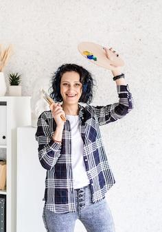Lächelnde künstlerin in ihrem studio, die kunstpalette und pinsel hält