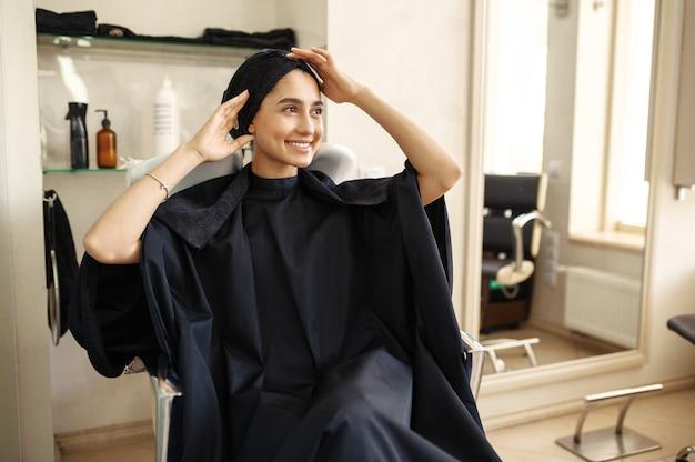 Lächelnde kundin im friseursalon. glückliche frau im friseursalon. schönheitsgeschäft, professioneller service, haarpflege