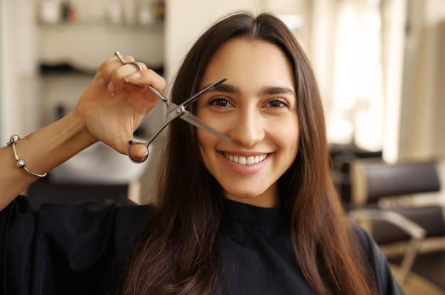 Lächelnde kundin mit sciccors im friseursalon. frau sitzt im stuhl im friseursalon. schönheits- und modegeschäft, professioneller service
