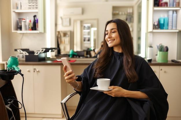 Lächelnde kundin mit telefon und tasse kaffee im friseursalon. frau sitzt im stuhl im friseursalon. schönheits- und modegeschäft, professioneller service