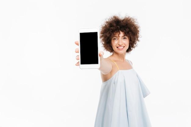 Lächelnde lässige frau, die handy des leeren bildschirms zeigt