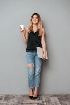 Lächelnde lässige frau, die laptop hält und kaffeetasse wegnimmt