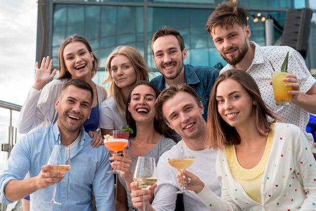 Lächelnde leute, die an einer party aufwerfen