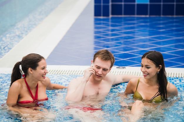Lächelnde leute mit handy im schwimmbad, das anruf macht. gesundheits-, entspannungs- und kommunikationskonzept