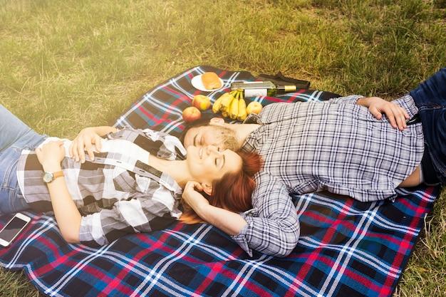 Lächelnde liebevolle junge paare, die auf decke über dem grünen gras liegen