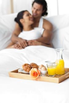 Lächelnde liebhaber, die auf dem bett frühstücken