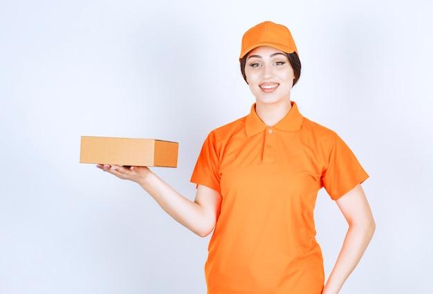 Lächelnde lieferfrau, die box auf sendung hält und nach vorne schaut