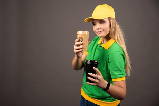 Lächelnde lieferfrau, die tassen kaffee auf schwarzer wand hält.