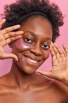 Lächelnde, lockige afroamerikanerin lächelt sanft, hält die hände in der nähe des gesichts und trägt schönheitsflecken auf