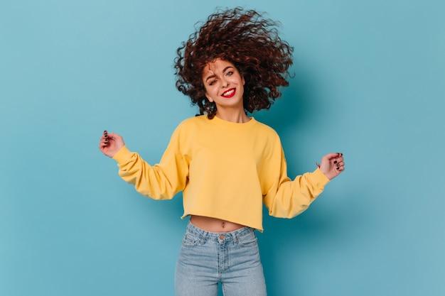 Lächelnde lockige frau mit roten lippen, gekleidet in gelbem pullover und röhrenjeans, die haare auf isoliertem raum spielen.