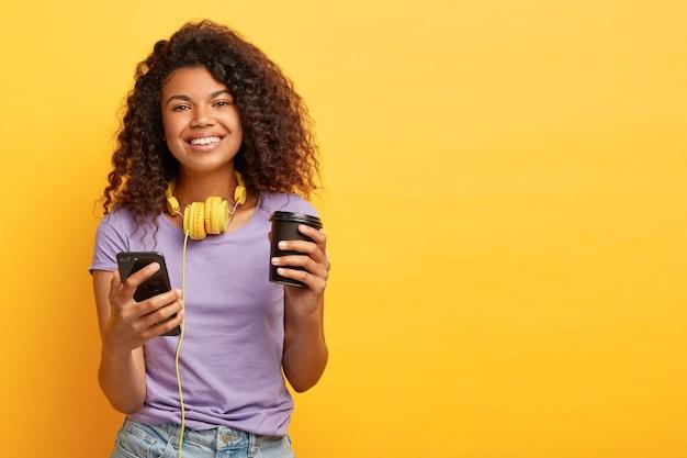 Lächelnde lockige frau sieht video auf handy während der kaffeepause, hört audiospuren über kopfhörer, hat gute laune, trägt lässiges outfit, isoliert über gelbem hintergrund, leerzeichen