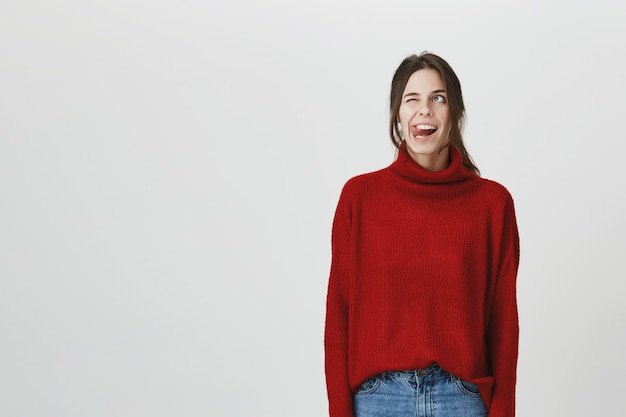 Lächelnde lustige frau zeigt zunge, lächelnder blick nach oben