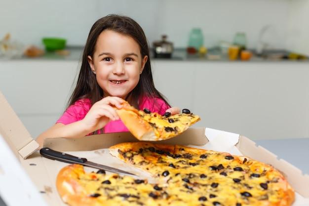 Lächelnde mädchen beim essen von pizza