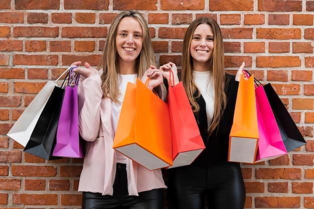 Lächelnde mädchen, die kamera beim halten von einkaufstaschen betrachten