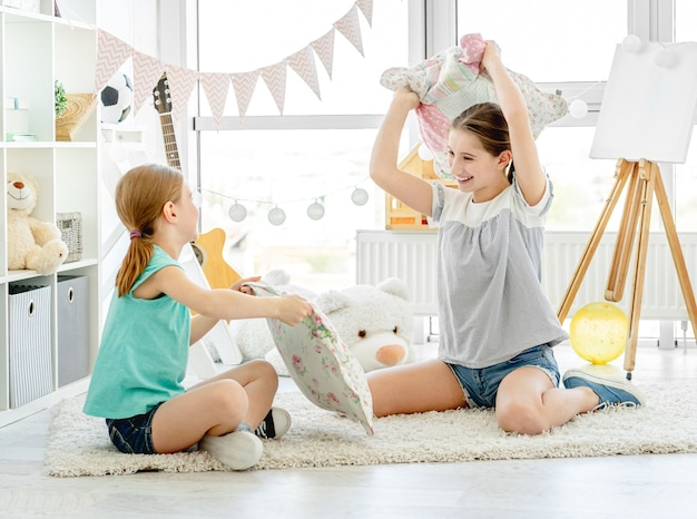 Lächelnde mädchen, die mit kissen im kinderzimmer kämpfen