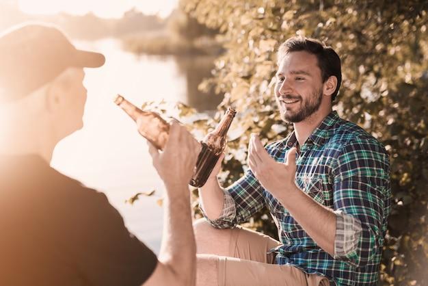 Lächelnde männer, die bier nahe fluss im sommer trinken.