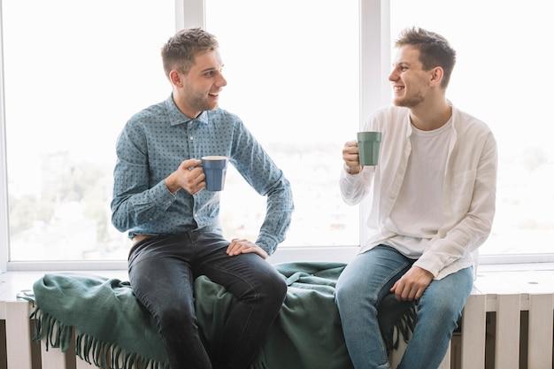 Lächelnde männliche freunde, die nahe dem fenster trinkt kaffee sitzen