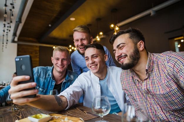 Lächelnde männliche freunde, die selbstporträt auf mobile im restaurant sprechen