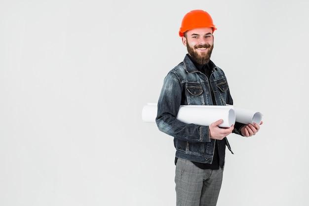 Lächelnde männliche ingenieurholding rollte herauf plan gegen weißen hintergrund