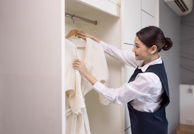 Lächelnde magd mit weißem bademantel mit kleiderbügel im kleiderschrank, das konzept der hotelbranche Premium Fotos