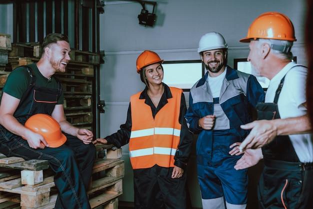 Lächelnde menschen in uniform und schutzhelmen in der pause