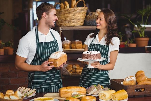 Lächelnde mitarbeiter, die brot und kuchen zeigen