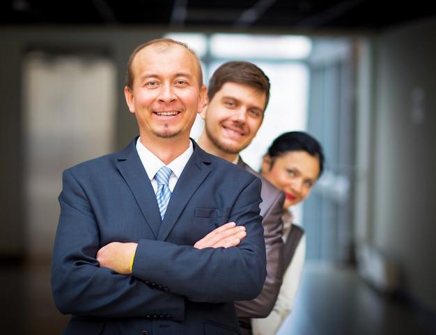Lächelnde mitarbeiter, die um ihren vorgesetzten herumstehen
