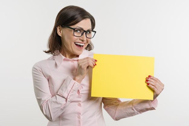 Lächelnde mittlere gealterte frau mit gelbem blatt papier