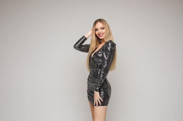Lächelnde modeblondine im schwarzen kleid, das kamera betrachtet
